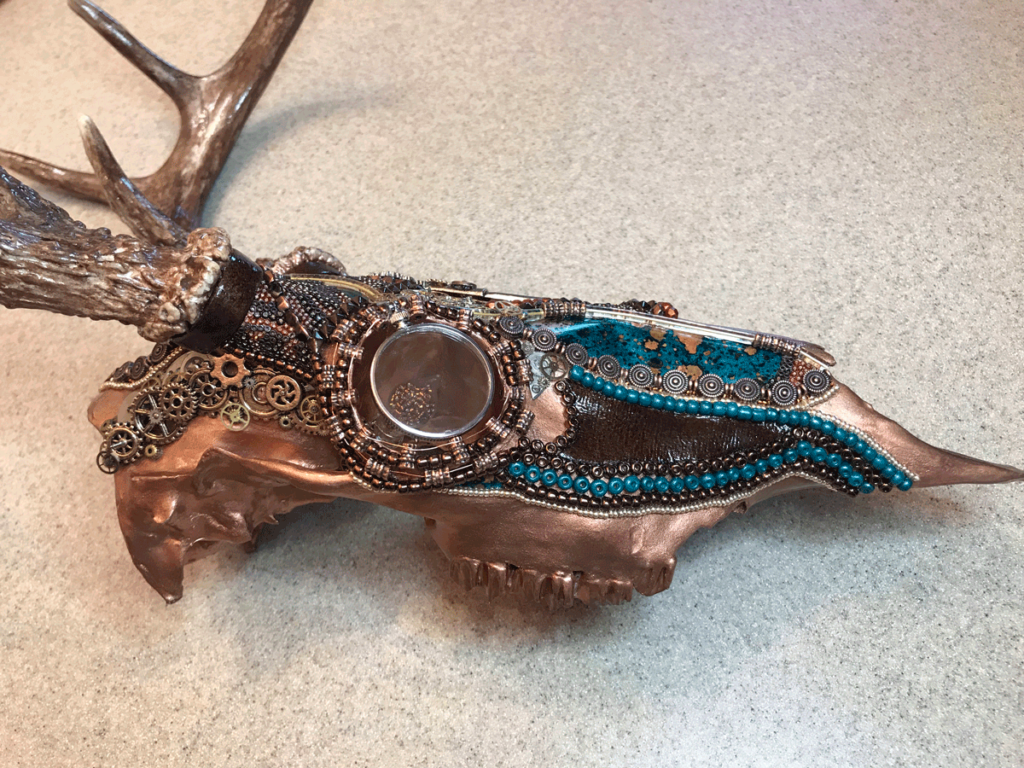 The finished Steampunk whitetail deer skull bead design, painted antlers and art piece name.